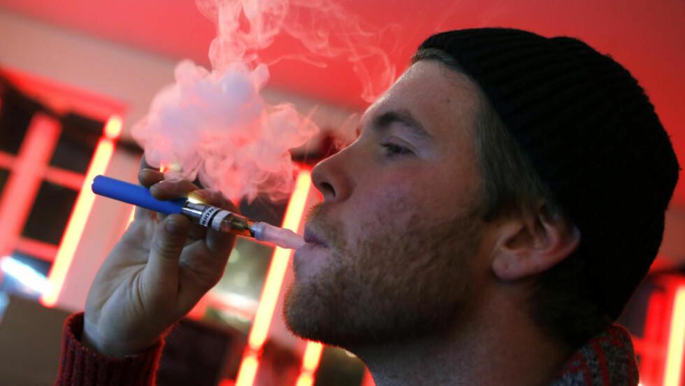 KONTROVERSIELL: En mann tester ut en e-sigarett på en bar i New York i fjor. Nå går diskusjonen høyt om hvilke stoffer de elektroniske sigarettene inneholder. Foto: Reuters / NTB Scanpix