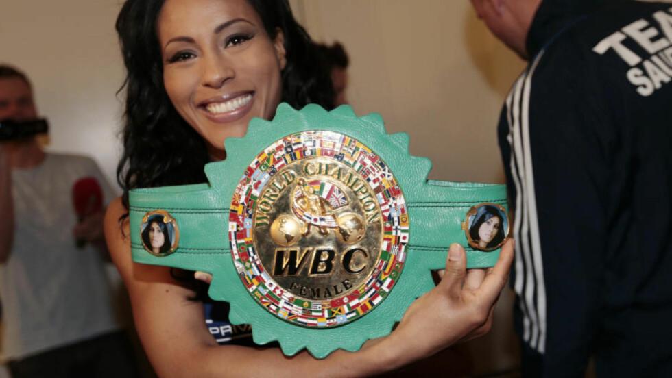 BEVISET: Cecilia Brækhus har fått spesialdesignet WBC-beltet sitt, med bilder av seg selv.  Foto: Lise Åserud / NTB Scanpix