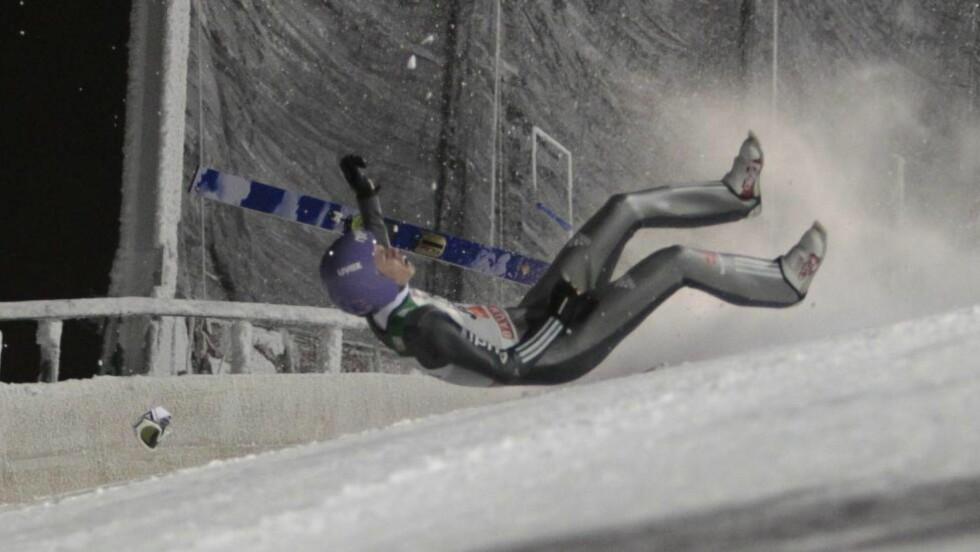 FALL: Andreas Wellinger fra Tyskland smeller i bakken i hoppbakken i Kuusamo. Foto:  EPA/PEKKA SIPOLA FINLAND OUT
