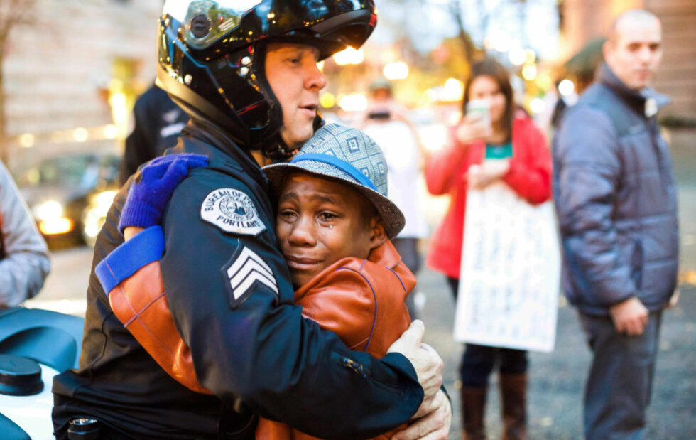 EN GOD KLEM: Bildet av politimannen Bret Barnum og Devonte Hart (12) har rørt nettbrukere USA og verden over. Foto: AP / Johnny Huu Nguyen / NTB scanpix