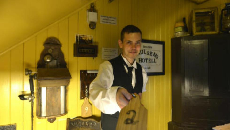 GAMMEL STIL: Ingen dørkort eller annet tull i den gulmalte resepsjonen til Paulsens Hotell. Her deler Arne Karlsen (27) ut gode, gammeldagse nøkler. Foto: GJERMUND GLESNES