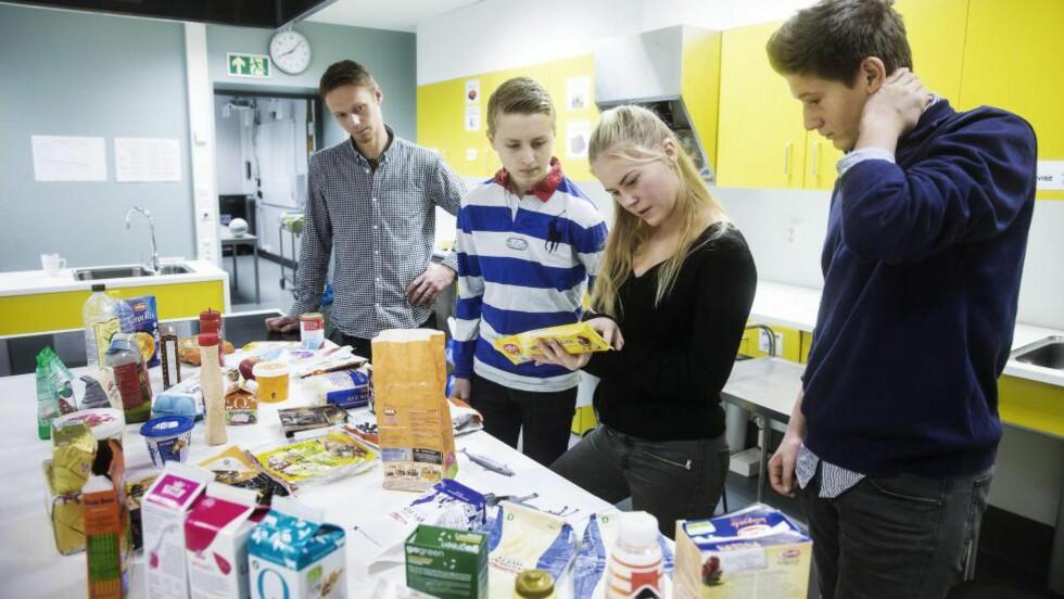 BLIR BEVISSTE: Oscar Thomsen (14), Mathilde Emilie Lindenskov (14) og Jacob Franquillo Hotvedt (14) ved Majourstuen skole har akkurat lært å lese bakpå matvarer i faget Mat og helse. De syns det er fint å lære om hva alt betyr. Lærer Oliver Madsen (34) syns det viktigste de lærer, er matglede. Foto: BJØRN LANGSEM