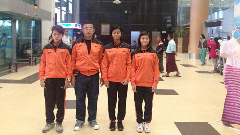 11 ÅR: De tre 11-åringene som forsvarer Myanmars ære under svømme-VM avbildet på flyplassen i Yangoon med en lagleder - før turen gikk til Doha. Foto: Myanmars svømmeforbund
