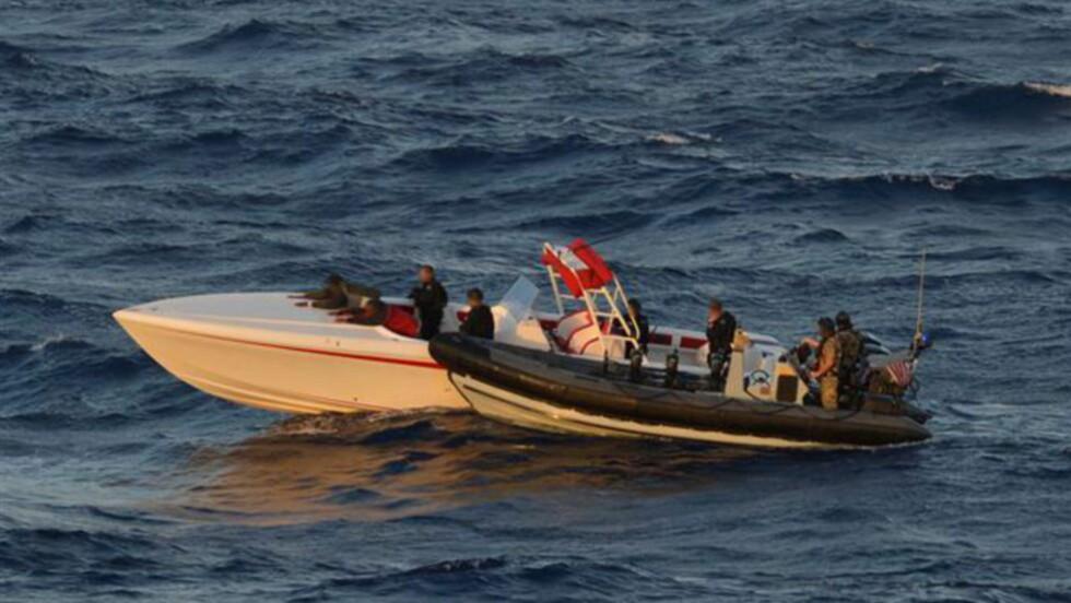 STANSET: De to smuglerne ligger framoverlent med begge hendene på dekket etter at skarpskyttere har ødelagt alle de tre motorene deres under båtjakten. Båten var lastet med 215 kilo kokain. Foto: US Southern Command