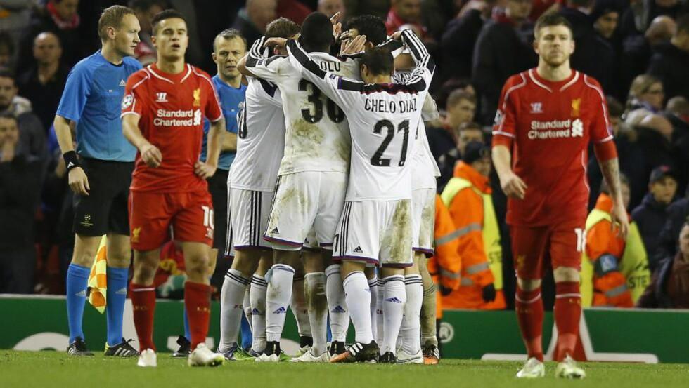 KONTRASTER: Basel-spillerne jublet vilt da sluttsignalet gikk på Anfield i går. Liverpools Coutinho (t.v.) og Alberto Moreno kunne ikke gjøre annet enn å fortvile. Foto: AP Photo / Jon Super / NTB Scanpix
