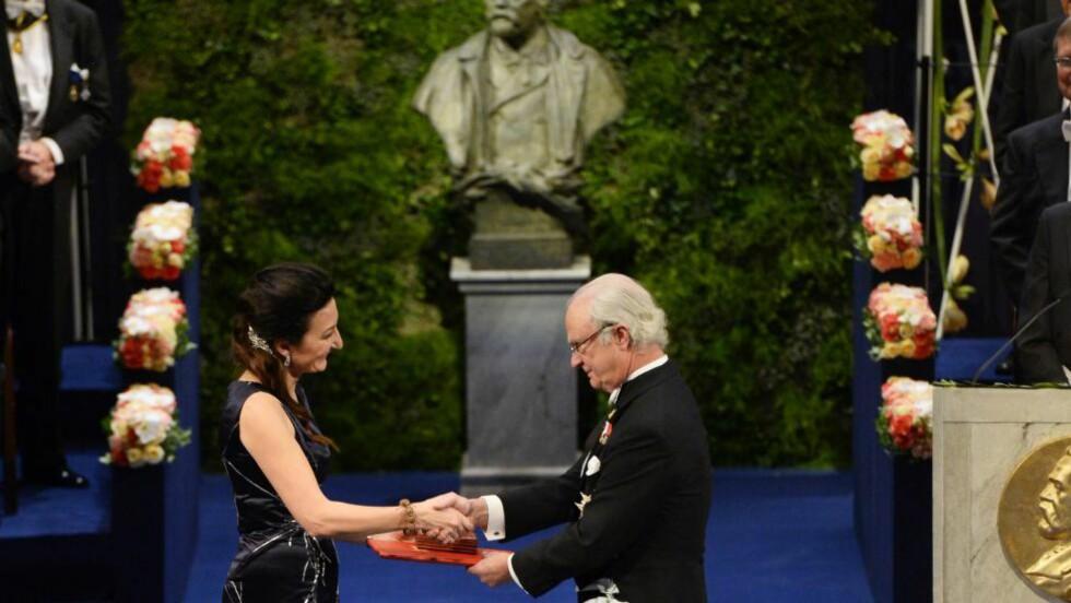 STORT ØYEBLIKK: May-Britt Moser tar svenskekongens hånd og blir overrakt Nobelprisen i medisin onsdag kveld. Foto: AFP  / JONATHAN NACKSTRAND
