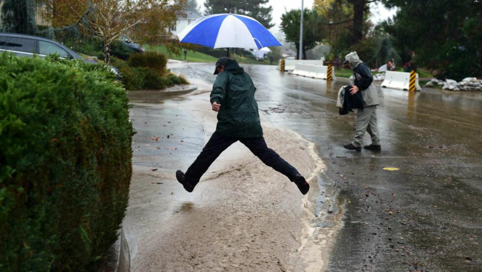 MISTET STRØM:  Titalls tusen amerikanere mistet strømmen idet regn, snø og vindkast på opptil rundt 64 meter per sekund feide innover den amerikanske delstaten torsdag. Her ser du regnet fosse ned langs gatene i Rainbow Drive i Glendora i California. Illustrasjonsfoto: NTB / AFP.