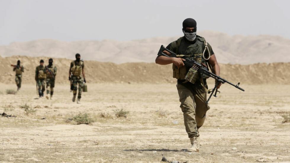 KJEMPER MOT IS: Milits fra Asaib Ahl al-Haq og Kurdiske peshmerga-styrker bærer på sine våpen etter å ha tatt kontroll over Sulaiman Pek fra IS 1. september. Foto: REUTERS/Youssef Boudlal