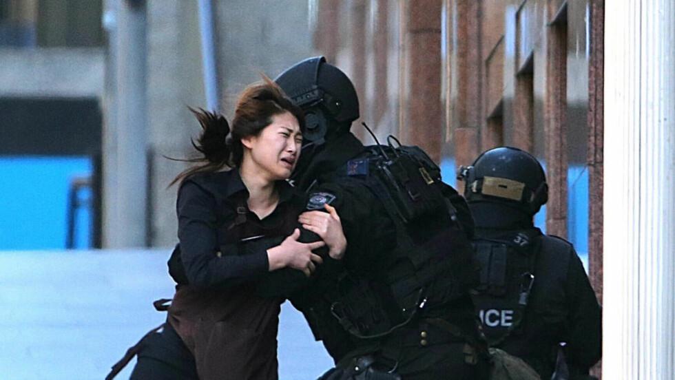 ETTER SJU TIMER:  En av de ansatte kommer seg i sikkerhet fra kafeen i Sydney. Foto: Rob Griffith, AP/NTB Scanpix.