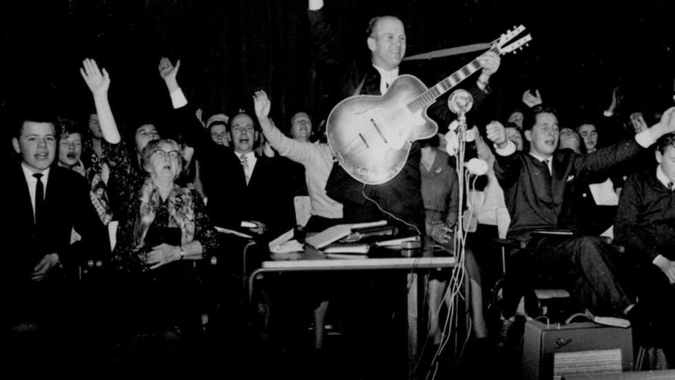 «HERRENS GLADE GUTT»: Den ukonvensjonelle vekkelsespredikanten Aage Samuelsen var en av de første i Norge som spilte el-gitar. Her på et møte i Oslo i 1956.