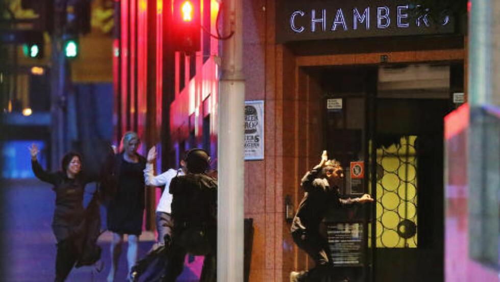 UNNSLAP GISSELTAKEREN:  Gisler løper i sikkerhet ut av Lindt Cafe etter politiet gikk til aksjon mot gisseltakeren Man Haron Monis som holdt 17 personer som gisler i 16 timer. Foto: Joosep Martinson / Getty Images