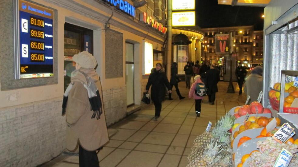VEKKER OPPMERKSOMHET :  En kvinne stanser opp for å sudere valuakursene i sentrum av St. Petersbyrg. Det koster 85 rubler å kjøpe en dollar. Mandag morgen kostet det 58. Foto: Irina Strand.