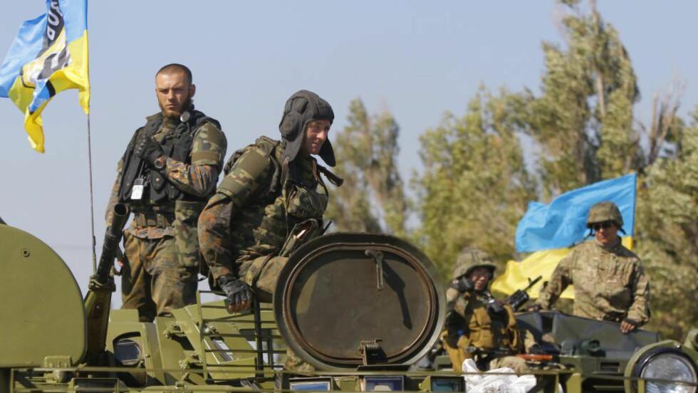 NYE KAMPER: Ukrainske soldater i havnebyen Mariupol mottok fredag nyheten om våpenhvilen mellom de prorussiske opprørerne og ukraniske myndigheter, og et foreløpig punktum for den fem måneder lange konflikten. Et drøyt døgn seinere meldes det igjen om kamper. Foto: Sergei Grits /AP