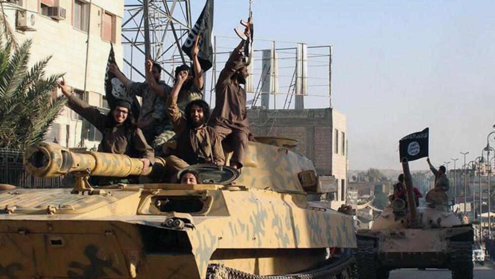 HOVEDKVARTER: Den islamske staten pareder i den syriske byen Raqqa i juni i år. Byen er blitt terrrorgruppens viktigste bastion. Foto: NTB scanpix