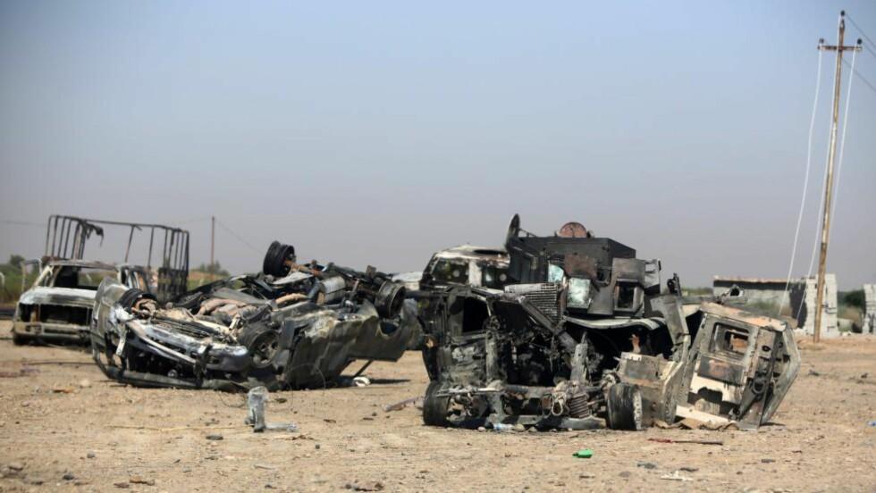 HARDE KAMPER: Utbrente biler ligger ved byen Samarra ved Haditha-demningen - et viktig strategisk mål både for IS og irakiske sikkerhetsstyrker. USA gjennomførte i dag bombeangrep mot IS ved demningen. Foto: NTB scanpix