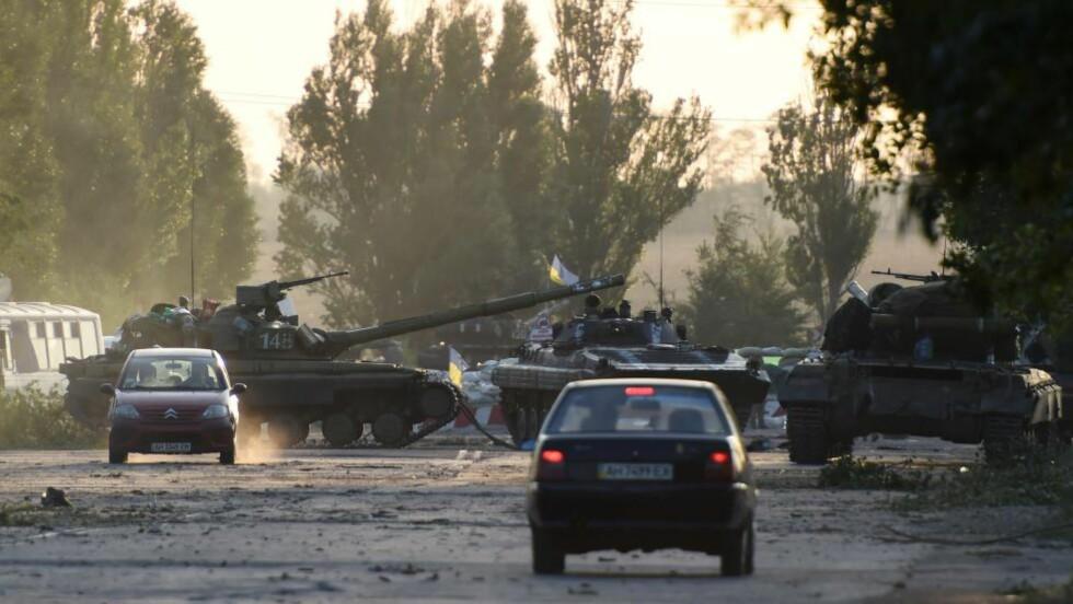 OPPTRAPPING: : Panservogner blokkerer veiene ved Mariupol øst i Ukraina tidligere i dag. Alt tyder på at kampene fortsetter i landet. Foto: AFP PHOTO / PHILIPPE DESMAZES