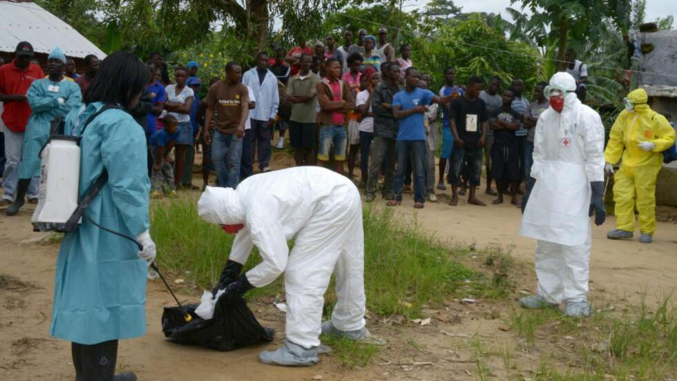 KRISEMØTE: Helsearbeidere fra Røde Kors i Liberia på jobb i et nabolag i Banjor i utkanten av Monrovia. Det tropiske viruset som smitter gjennom kroppsvæsker har drept om lag 2100 mennesker i fire land, nmer enn halvparten av dem i Liberia. Foto: AFP / Scanpix  / DOMINIQUE FAGET