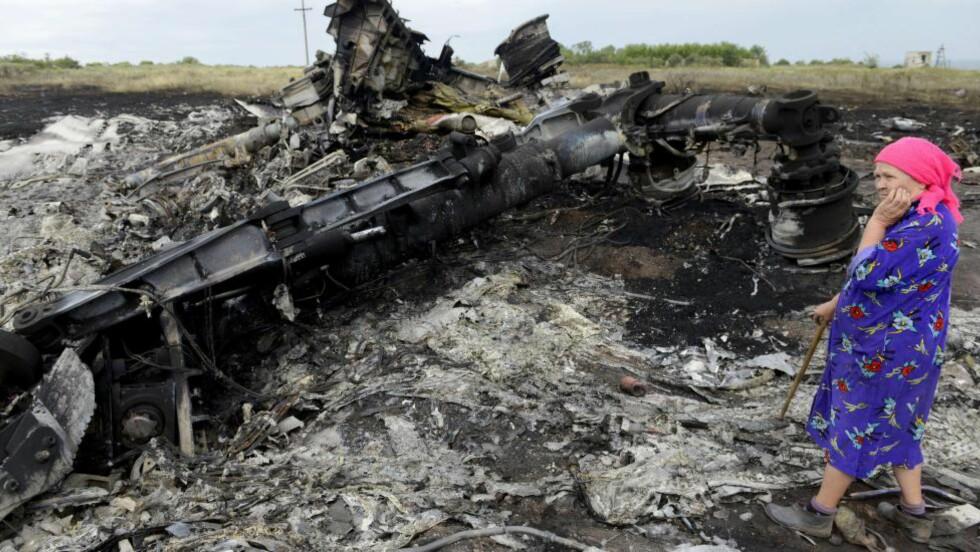 NY RAPPORT:  En lokalinnbygger ved vraket til MH17 den 19. juli i år. Tirsdag offentliggjorde nederlandske myndigheter sin foreløpige rapport. Foto: AFP/ALEXANDER KHUDOTEPLY