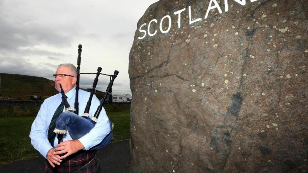 SPENNENDE TIDER: Neste torsdag skal det velges om Skottland fortsatt skal være avhengig eller uavhengig av regjeringen i London. Her spiller Allan Smith sekkepipe på grensen mellom England og Skottland. Foto: AP/NTB Scanpix