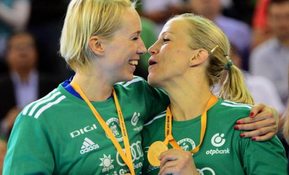 GULLJENTER: Heidi Løke (t.h) og Katrine Lunde i en munter stemning etter at Györ vant Champions League-finalen i sommer, i samme hall som Løke og håndballjentene skal spille semifinale mot Sverige i i kveld. Foto: NTB Scanpix