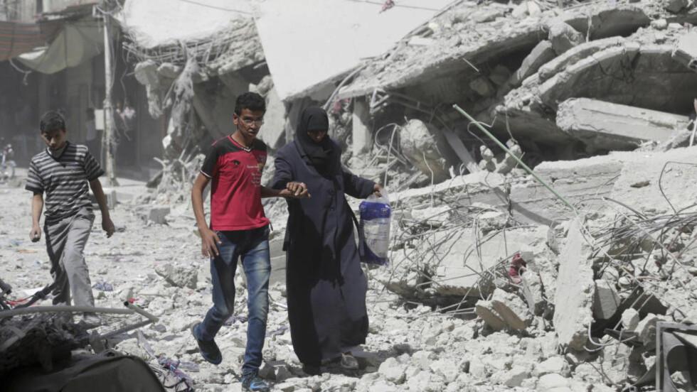 MANGE SULTER: Innbyggere i Douma utenfor Damaskus går forbi bygninger som ifølge innbyggere er lagt i grus i flyangrep i regi av styrkene til president Bashar al-Assad. Nå varsler FN at det ikke kommer inn nok penger til å fortsette matleveransene til de mange som er avhengig av nødhjelp i Syria. Foto: Bassam Khabieh / Reuters / NTB Scanpix