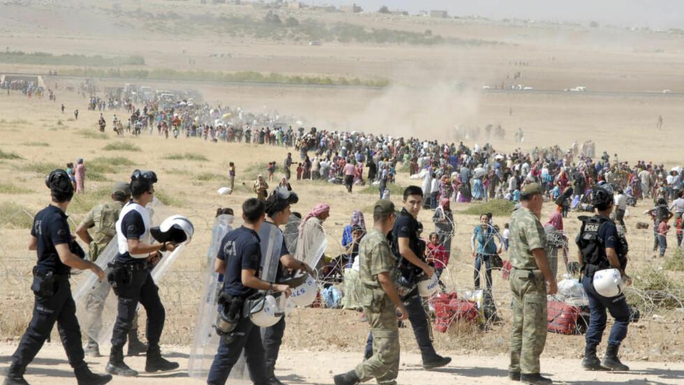 RØMMER FRA IS:  Bildet er fra i dag og viser kurdiske flyktninger som venter på å komme over grensen til nabolandet i nord, Tyrkia. Foto: REUTERS/Stringer