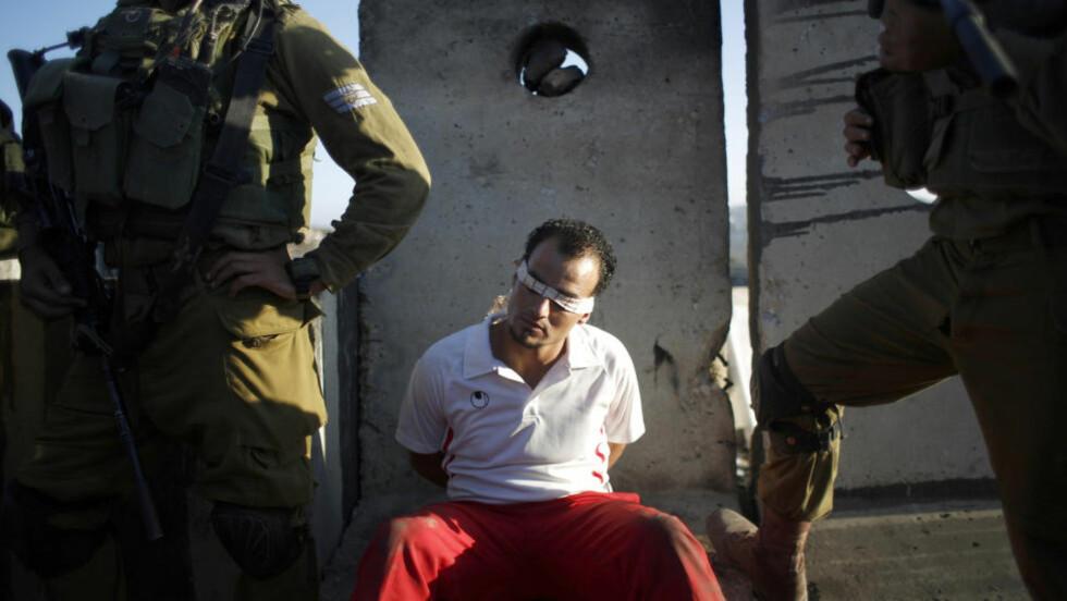 KRIG: Kidnappingen og drapet på tre israelske ungdommer dannet noe av bakgrunnen for den sju uker lange krigen i Gaza i sommer, der over 2000 mennesker ble drept. Her har israelske soldater tatt en palestiner til fange på Vestbredden tidligere i september. Foto: Reuters / NTB scanpix