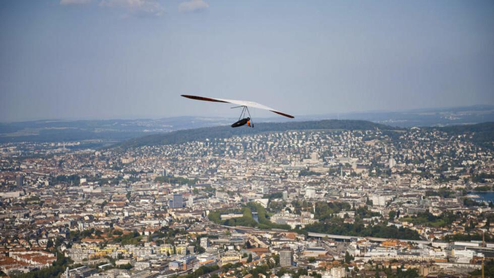 GOD UTSIKT: Denne paraglider-piolten har godt utsyn over den største byen i Sveits. Hva heter den? Foto: Håkon Eikesdal