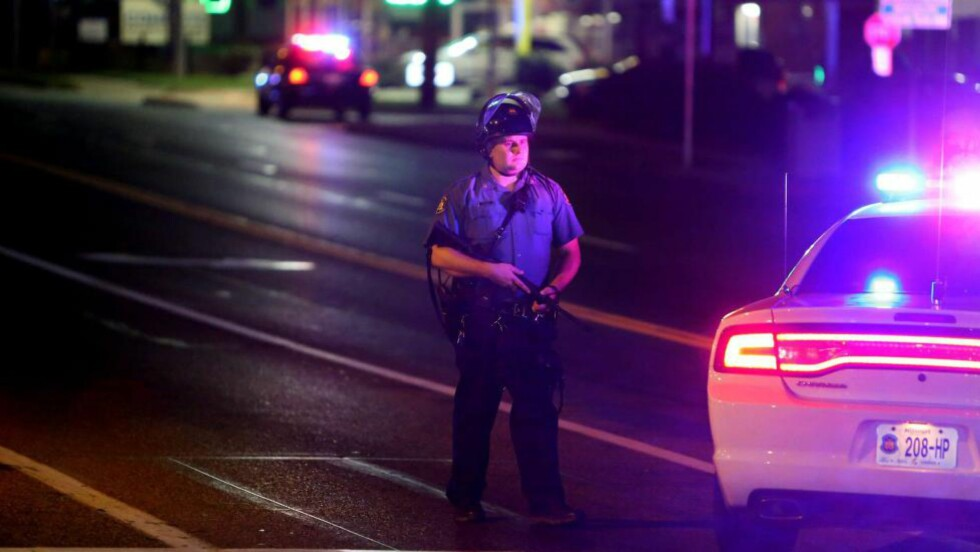 OPPTØYER: En politimann holder vakt i Ferguson i Missouri, der en annen politimann ble skutt sent lørdag kveld. Byen har vært åsted for en rekke opptøyer etter at svarte Michael Brown (18) lørdag 9. august ble skutt og drept av en hvit politimann. Foto: David Carson/AP/St. Louis Post-Dispatch/Scanpix