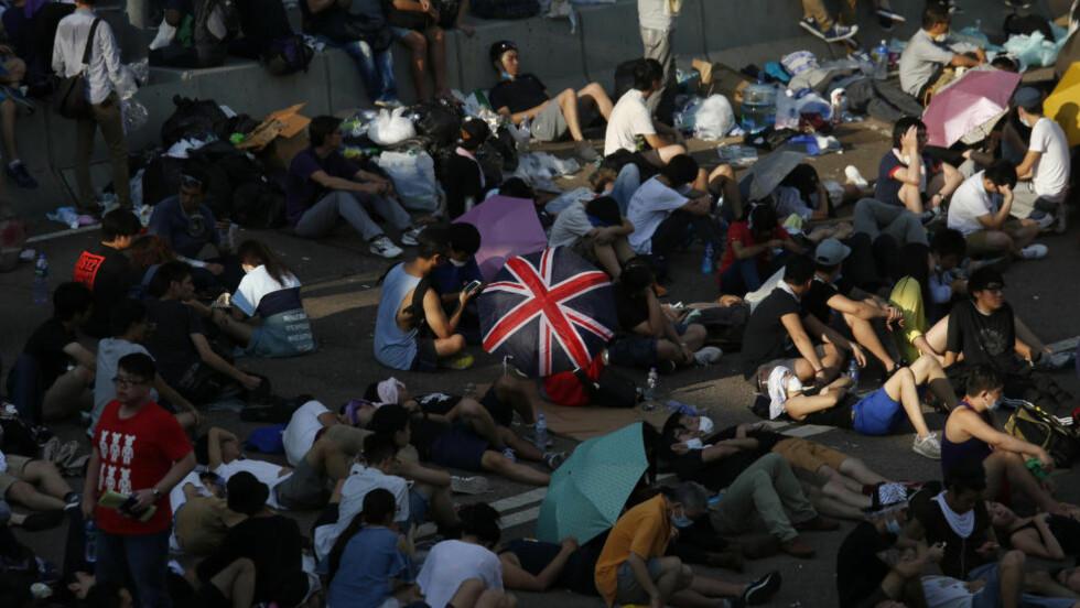 STOPPER TRAFIKKEN:  Demonstrasjonen sitter i hovedgaten som går gjennom Hongkongs finansdistrikt mandag morgen. Foto: Bobby Yip / Reuters / NTB Scanpix