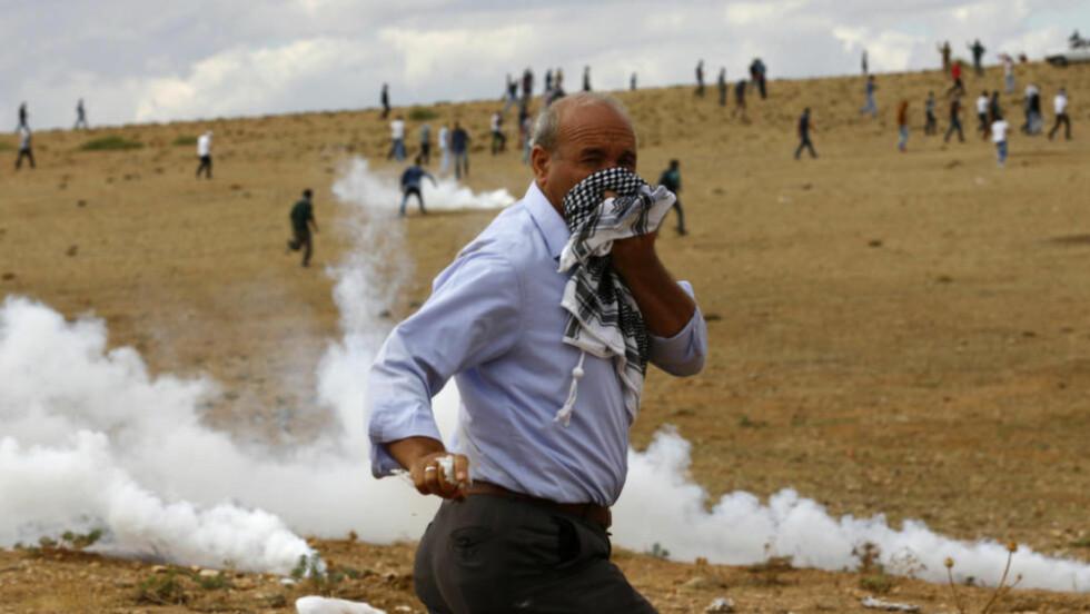 PROTESTERER: En tyrkisk kurder løper vekk fra tåregassen som tyrkisk politi har brukt mot demonstrasjonene langs den tyrkisk-syriske grensen i den sørøstlige byen Suruc. Foto: Murad Sezer / REUTERS / NTB Scanpix.