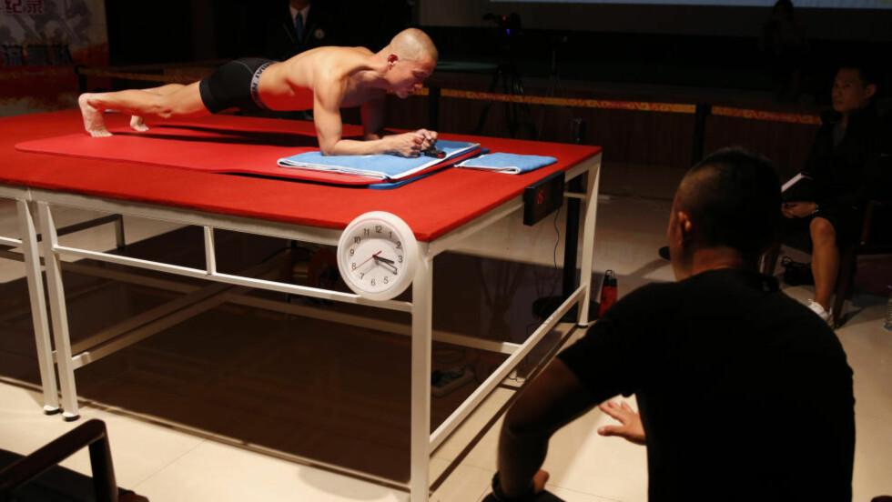 NY VERDENSREKORD:  Mao Weidong fra Beijing SWAT satte fredag ny verdensrekord i planking, ved å stå fire timer og 26 minutter i planken ved SWATs treningslokaler utenfor Beijing. Foto: Vincent Thian / AP Photo / NTB Scanpix