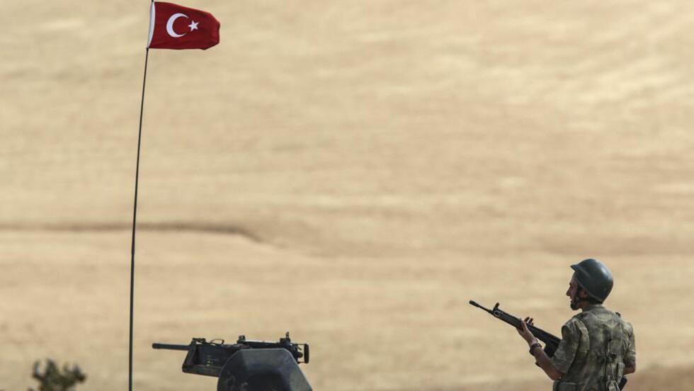 GRENSA: Det er kamper i Syria, svært nær den tyrkiske grensa, hvor en tyrkisk soldat her står klar. Tyrkias nasjonalforsamling ga i dag regjeringen tillatelse til å kunne delta i kamper i Irak og Syria. Foto: AFP / BULENT KILIC / NTB SCANPIX