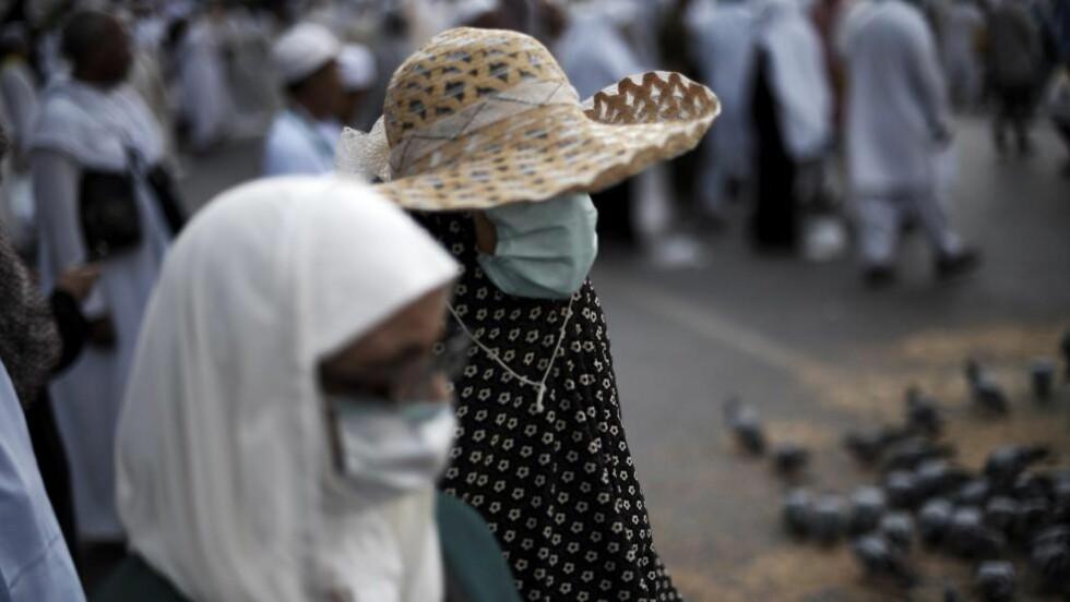 FØRE VAR: Muslimske pilgrimmer kommer til Mekkas hellige moské iført munnbind. Årets pilgrimsferd skaper utfordringer i å hindre at de to dødelige sykdommer ebola og MERS (Middle East Respiratory Syndrome). Foto: Mohammed Al-Shaikh/AFP/Scanpix