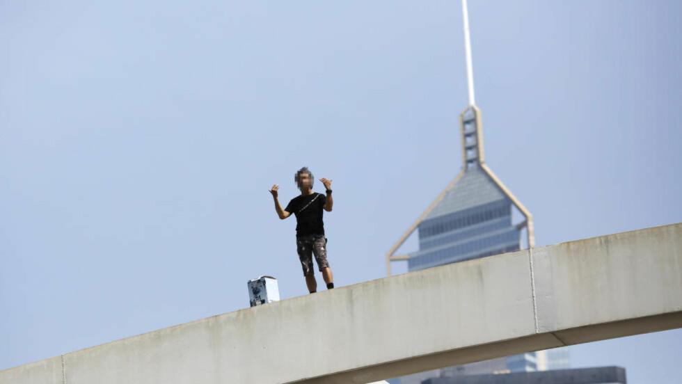 TRUET MED Å HOPPE: Denne mannen truet med å hoppe hvis ikke demokratidemonstrantene fjernet veisperringer og barrikader i nærheten av regjeringsbygget. Foto: Reuters / NTB Scanpix