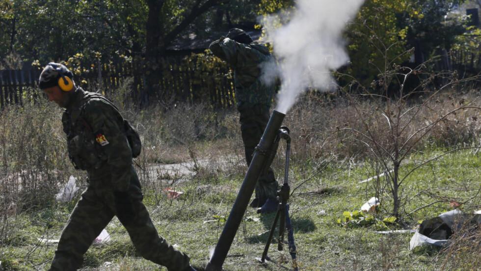 VÅPENHVILE: Dette bildet fra onsdag viser prorussiske opprørere som avfyrer granater mot ukrainske stillinger i nærheten av flyplassen i Donetsk. Kampene i byen fortsetter til tross for våpenhvilen fra 5. september. Foto: Dmitry Lovetsky/AP/Scanpix