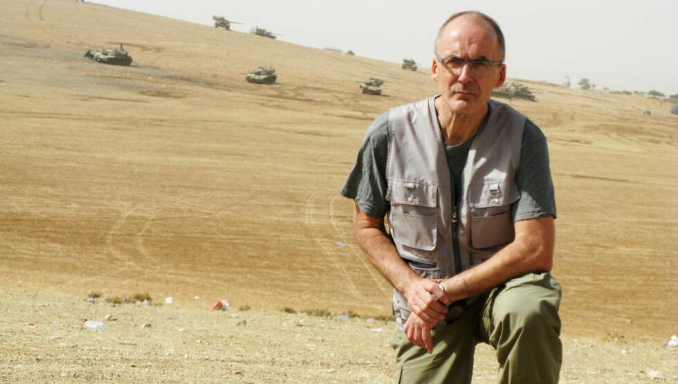 TROR TYRKERNE VIL INVADERE: Rødt-politiker Erling Folkvord foran tyrkiske tanks oppstilt rett foran grensa ved Kobani. Han tror panservognene er klare til å innta byen - men først etter at IS har beseiret kurderne. Foto: SVEIN OLSEN