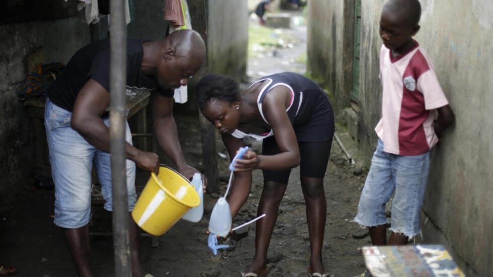 BEHANDLING HJEMME:  En jente fyller opp bøtta med klorløsning for deisinfisering i Monrovia i Liberia. Fredag godkjente myndighetene planer om å la familiene behandle ebola-pasienter hjemme. Foto:AP Photo/Jerome Delay/NTB Scanpix