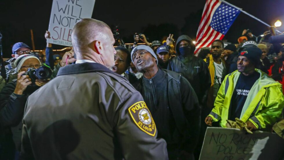 PROTESTERER: Flere hundre personer protesterte fredag kveld utenfor politistasjonen i Ferguson i Missouri, etter at en politimann onsdag avfyrte 17 skudd mot en 18-åring i St. Louis. Foto: TANNEN MAURY/EPA/SCANPIX