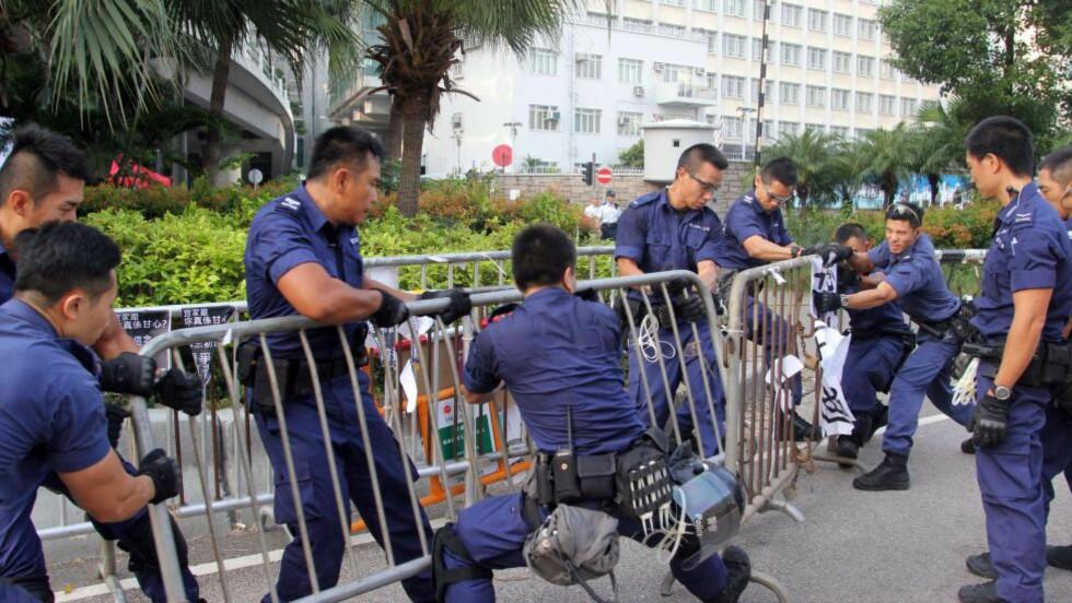 FJERNER: Politiet i Hong Kong fjernet barrikader nær regjeringskontorene der demokratiforkjempere har demonstrert i to uker.  AFP PHOTO / Laurent FIEVET