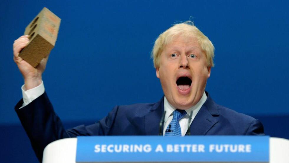 VIL BYGGE NYE HUS: Når ordfører i London, Boris Johnson, blir spurt om hans utenomekteskapelige forhold vil blir et problem for han som statsminister, svarer han at «folk er mer opptatt av hvordan man bygger nye hjem i London, bekjemper kriminalitet, og reduserer forskjellen mellom rik og fattige». Her holder han en murstein under landsmøte i partiet for å vise at han vil bygge flere hjem. Foto:  EPA/FACUNDO ARRIZABALAGA/NTB SCANPIX