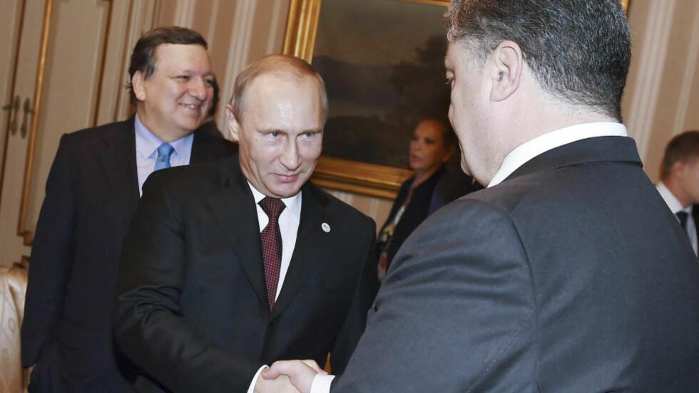 KONSTRUKTIVE SAMTALER: Putin og Porosjenko er i den italienske byen Milano i forbindelse med toppmøtet mellom asiatiske og europeiske land (ASEM). Bildet viser de to statslederne før møtet fredag morgen. Foto: Daniel Dal Zennaro/Reuters/NTB scanpix