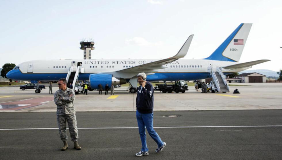 TRØBBEL PÅ FLYPLASSEN: USAs utenriksminister John Kerry må stadig booke seg inn inn på kommersielle rutefly for å komme hjem, ettersom hans eget, populært kalt «Kerry Air» (i bakgrunnen), stadig oftere går i stykker. Bildet er fra en mindre problematisk reise, der ministeren venter på at flyet skal tankes før avgang fra Ramstein i Tyskland. Foto: AP Photo/Lucas Jackson/NTB Scanpix