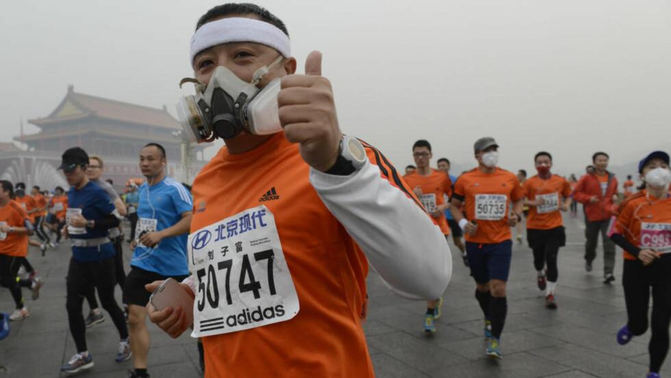 MASKE:  En av deltakerne i Beijing-maraton løper med maske. Foto: NTB Scanpix