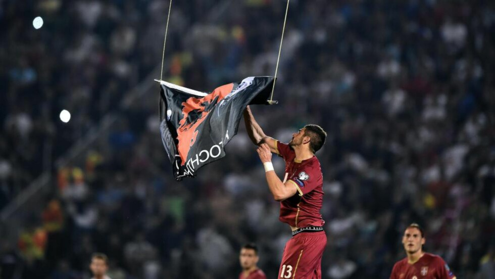 Serbia's Stefan Mitrovic grabs a flag with Albanian national symbols flown by a remotely operated drone during the Euro 2016 group I football match between Serbia and Albania in Belgrade on October 14, 2014. AFP PHOTO / ANDREJ ISAKOVIC