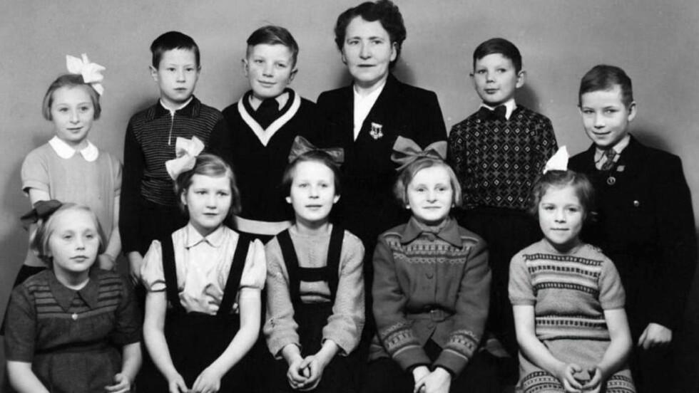 TUNELLBARNA: Bak fra venstre: Wenche Karen (Hansen) Leitman, Harald Randa, Bjørn Tunstad, jordmor Nelly Lund, Wernar Pedersen, Åge Johansson. Foran fra venstre: Else (Nyland) Bergan), Ebba (Sæther) Guntner, Sissel (Wilhelmsen) Fredriksen, Lillian Hardie og Sissel (Hansen) Johnsen. Nylig ble det kjent at det ble født 11 barn i tunellen, og at det derfor mangler ett barn på dette bildet.  Foto: Privat