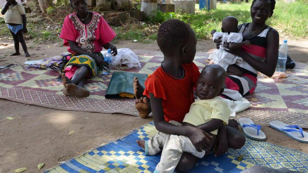 FORTVILT: Den lille gutten som sitter på storesøsters fang behandles for malaria i et barnesykehus i Juba i Sør-Sudan. En FN-ekspert frykter nå at malaria vil vokse igjen etter fokuset på ebola. Foto: Reuters / NTB scanpix
