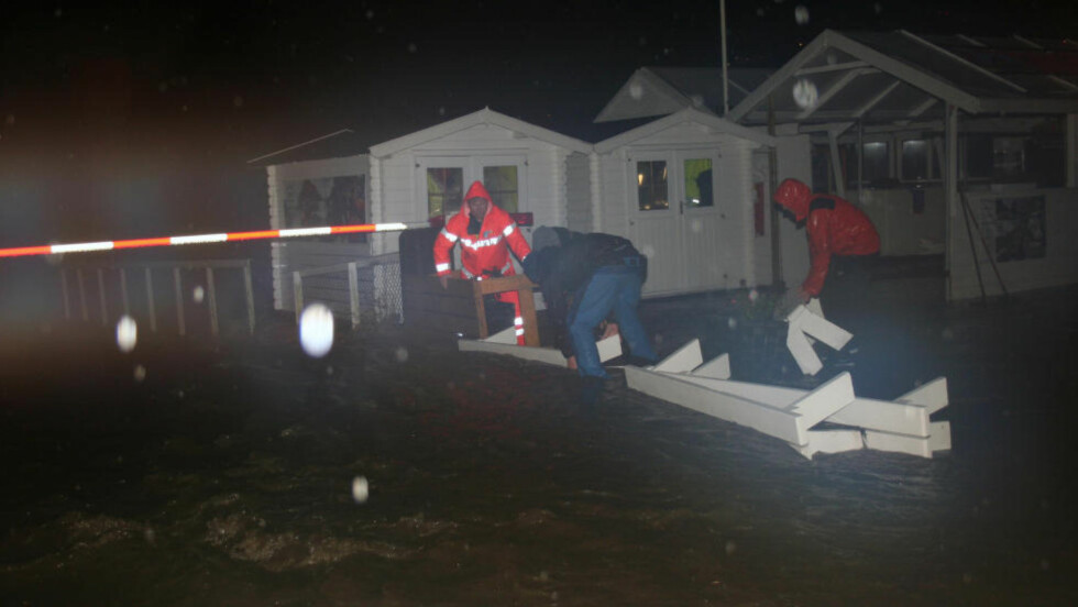 DRAMATISK: Flåm ble bokstavelig talt oversvømt tirsdag ettermiddag. 200 personer er evakuert fra bygda. Ansatte i Flåm Guide Service prøver her å lede vann vekk fra basen sin ved kaia. Foto: Arne Veum / NTB scanpix