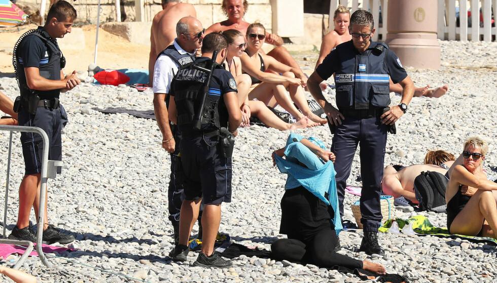 FORBUD: Fire politimenn konfronterte kvinnen, og ba henne fjerne den omstridte burkinien. Foto: Stella Pictures