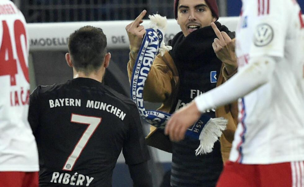 SLO: Bayern-spiller Franck Ribery ble slått av en Hamburg-supporter som stormet banen. Sekunder senere kom denne gesten banestormeren. Foto: REUTERS/Fabian Bimmer